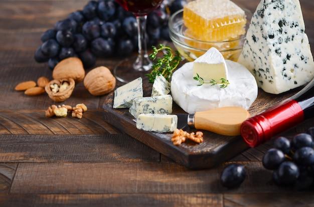 Käseplatte mit trauben, honig, nüssen und rotwein auf einem holztisch