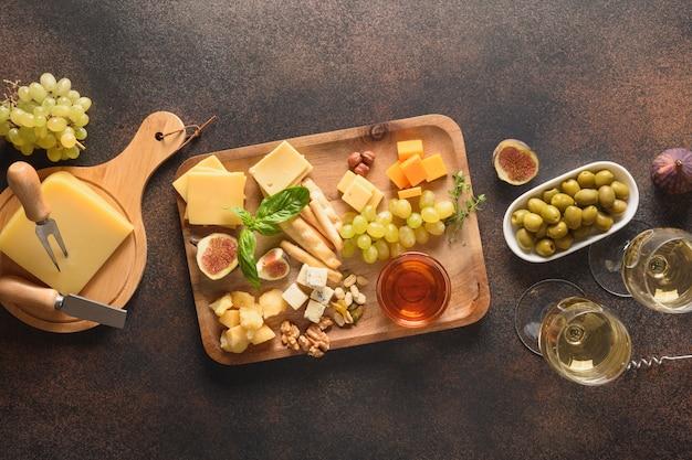 Käseplatte mit trauben nüsse feigen auf braunem hintergrund draufsicht