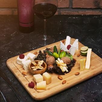 Käseplatte mit verschiedenen käsesorten, trauben, nüssen, honig, brot und datteln aus rustikalem holz. auf dunklem holzbrett mit weinflasche und glas wein