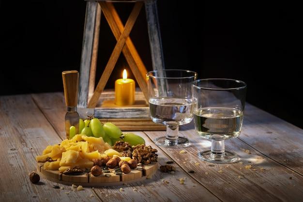 Käseplatte mit verschiedenen snacks auf dem tisch mit zwei gläsern wein bei kerzenschein