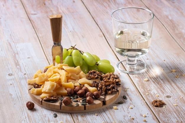Käseplatte mit verschiedenen snacks auf einem holztisch mit einem glas wein
