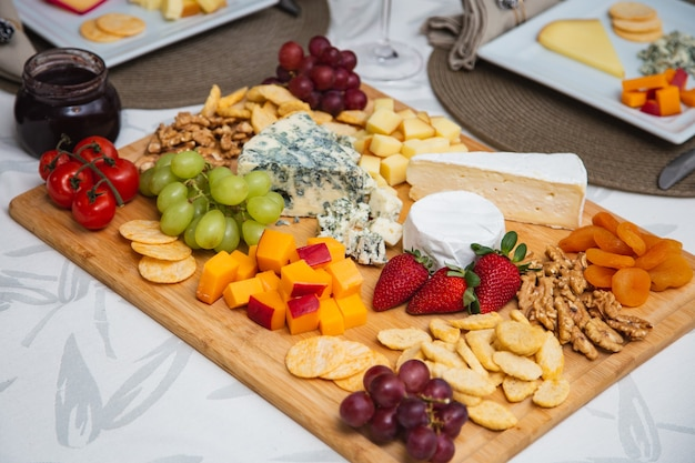 Käseplatte mit verschiedenen vorspeisen auf dem tisch. erdbeer-, aprikosen-, trauben- und körnerkäsegerichte auf dem tisch