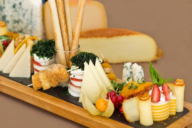 Käseplatte: roquefort mit blauem schimmel, cheddarkäse, geräuchertem käse, mozzarella auf einem holzbrett.