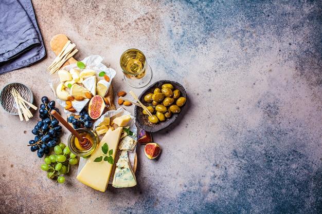 Käseplatte serviert mit früchten, honig und snacks, draufsicht. sortierter käsehintergrund.