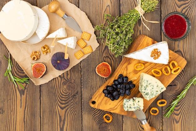 Käseplatte serviert mit marmelade, feigen, crackern und kräutern auf holz