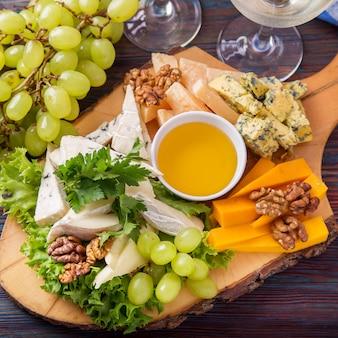 Käseplatte serviert mit weißwein, trauben und nüssen.