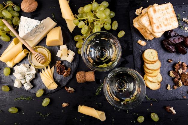 Käseplatte. zusammenstellung des käses mit walnüssen, brot ein honig auf steinschieferplatte.