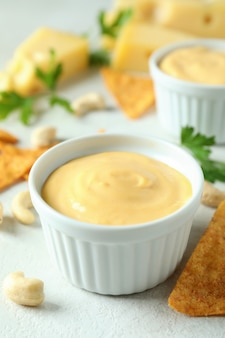 Käsesauce und snacks auf weißem strukturiertem tisch