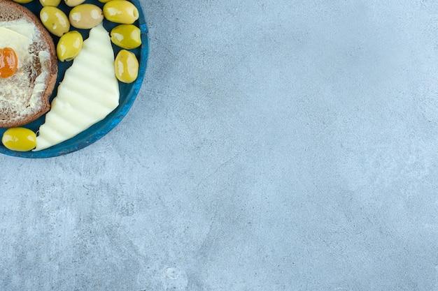 Käsescheibe, butterbrot und grüne oliven auf einer platte auf marmortisch.