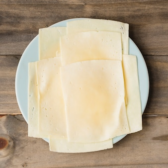 Käsescheiben auf weißer platte gegen hölzernen plankenhintergrund