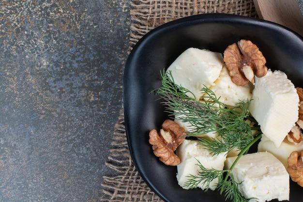 Käsescheiben, dill- und walnusskerne in schwarzer schüssel.
