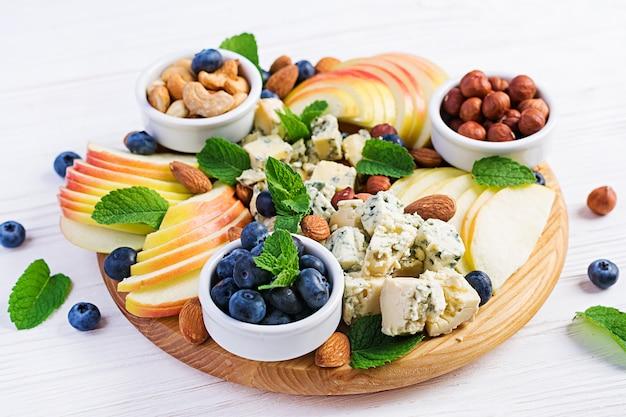 Käseservierplatte mit sortierten käsen, blaubeere, äpfeln, nüssen auf weißer tabelle. italienische käseplatte und obst.