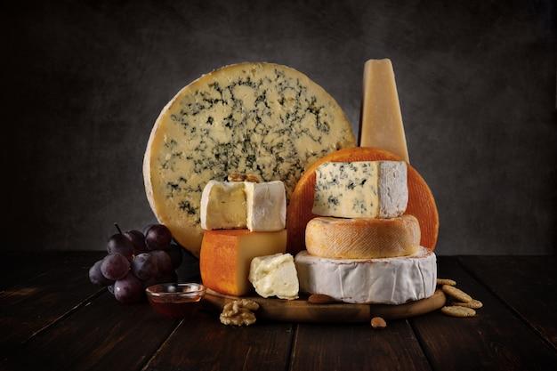 Käsesorte auf einem holzbrett mit nüssen und honig