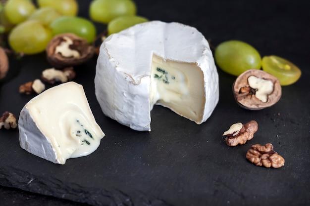 Käsesorte brie. weichkäse mit trauben und walnüssen auf schwarzem hintergrund