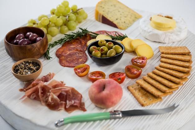 Käsesorte mit trauben, oliven, salami, crackern und messer