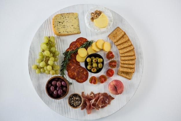 Käsesorte mit trauben, oliven, salami und crackern auf holzbrett