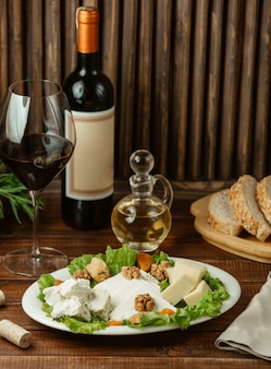 Käsesorten serviert mit walnüssen und einem glas rotwein