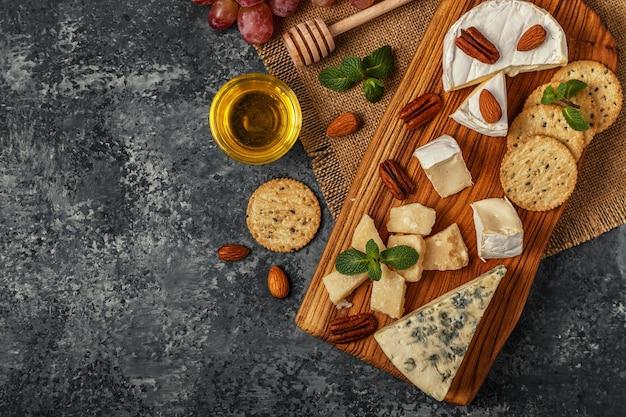 Käsesortiment mit honig, nüssen und trauben auf einem schneidebrett