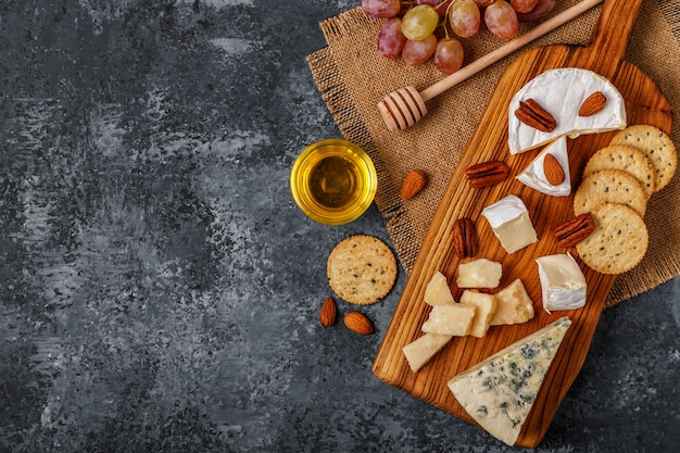 Käsesortiment mit honig, nüssen und trauben auf einem schneidebrett.