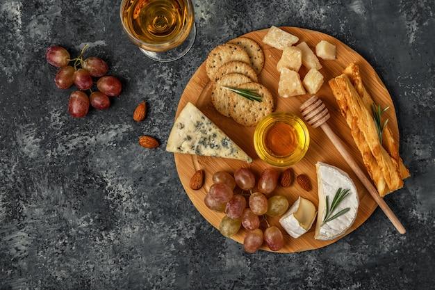 Käsesortiment mit wein, honig, nüssen und trauben auf einem schneidebrett.