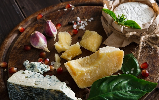Käsespezialitäten auf rustikalem holz, blauem roquefort, brie und parmesan