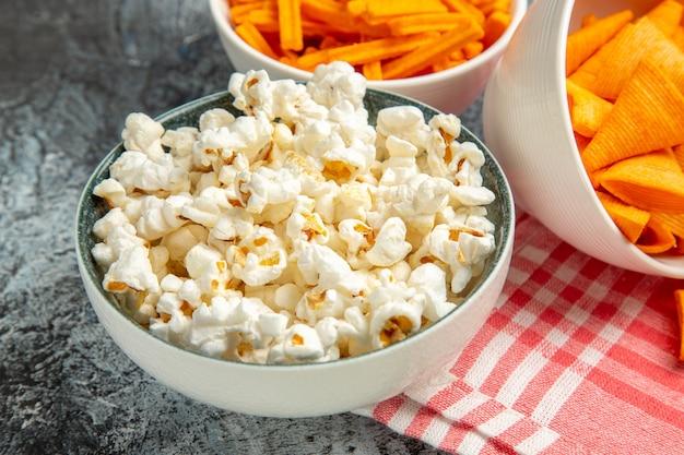 Käsespitzen der vorderansicht mit zwieback und popcorn auf dem hellen hintergrund