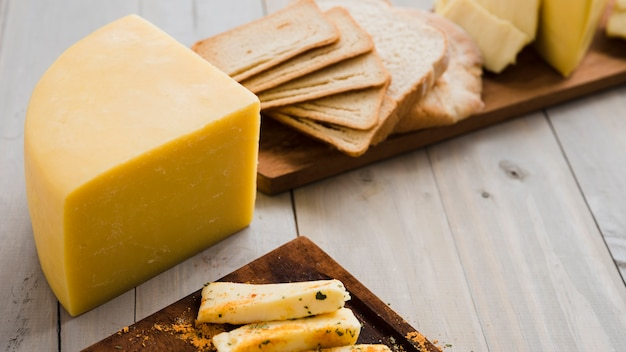 Käsestück- und -brotscheiben auf hölzernem brett über der tabelle