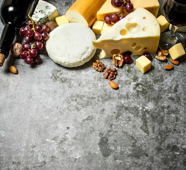 Käsestücke mit rotwein und nüssen. auf dem steintisch.