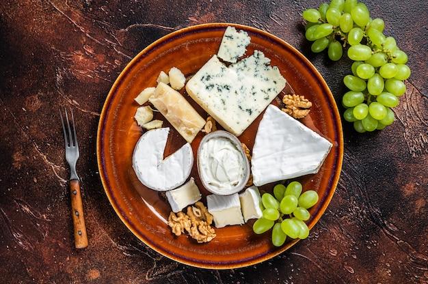 Käseteller mit brie, camembert, roquefort, blauschimmelkäse, trauben und nüssen.