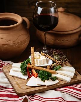 Käseteller mit knusprigem brot und einem glas wein