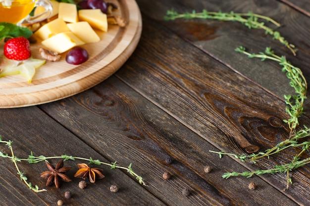 Käseteller mit kräutern auf hölzernem schreibtisch