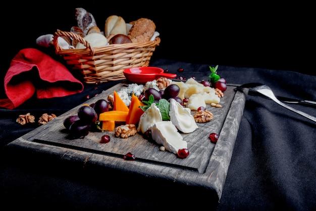 Käseteller serviert mit trauben, honig und nüssen. verschiedene käsesorten