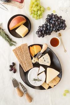 Käsetellersortiment mit honig, trauben, brot und rosmarin