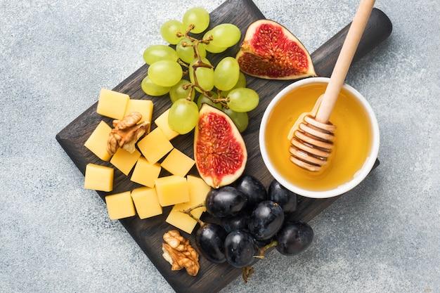 Käsewürfel, feigen aus frischen früchten honig-walnuss auf holzschneidebrett. copyspace.
