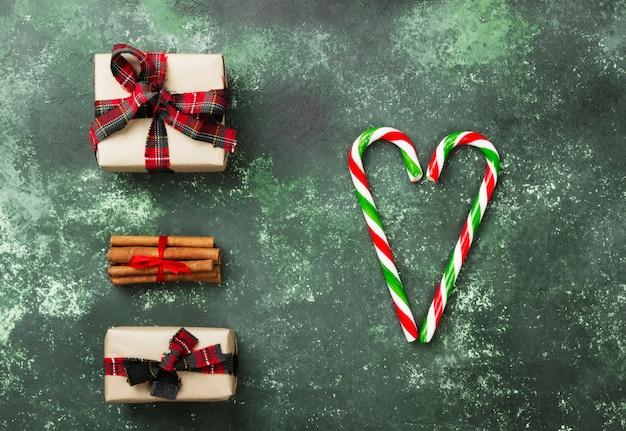 Kästen mit geschenken für weihnachten und herz von den zuckerstangen auf einer grünen oberfläche