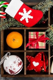 Kästen mit geschenken für weihnachten und verschiedenen attributen des feiertags auf einer dunklen oberfläche