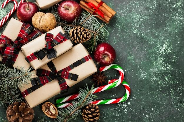 Kästen mit geschenken für weihnachten und verschiedenen attributen des feiertags auf einer grünen oberfläche