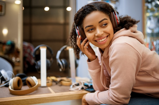 Käufer, der kopfhörer im audiogeschäft, musikfan wählt. weibliche person im musikgeschäft, schaufenster mit kopfhörern, frau im multimedia-geschäft