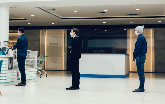 Käufer in schutzmasken stehen in einer warteschlange in einem supermarkt