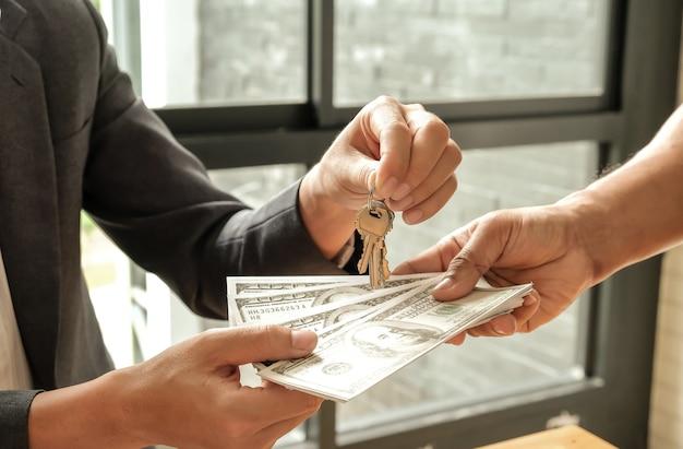 Käufer und verkäufer geben dollargeld, verkäufer geben schlüssel.