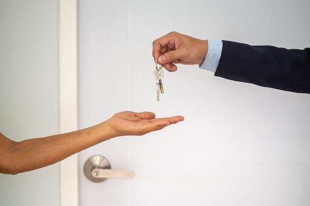 Käufer von eigenheimen nehmen schlüssel von verkäufern mit nach hause