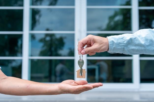 Käufer von eigenheimen nehmen schlüssel von verkäufern mit nach hause.