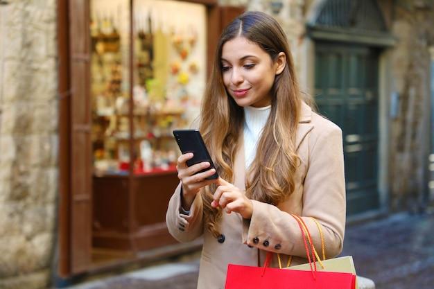 Käuferfrau, die produkt für online-kauf auf smartphone in der stadtstraße wählt.