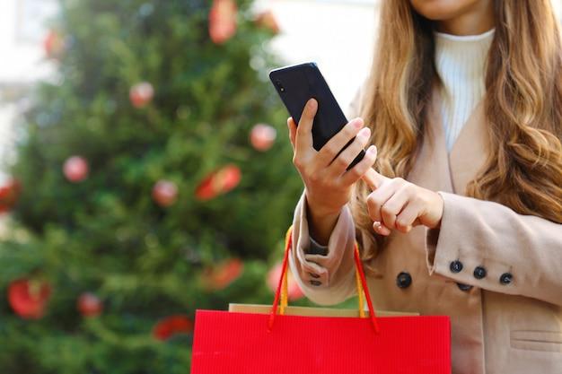 Käuferfrau, die smartphone zum online-einkauf und zum tragen von taschen zur weihnachtszeit verwendet.