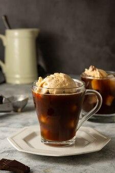 Kaffee affogato kaltes sommergetränk. kaffeetasse mit eisportionierer, dessert. dunkler hintergrund.