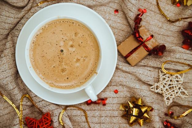 Kaffee auf einem hintergrund des gestrickten stoffes mit geschenken und feiertagsschleifen