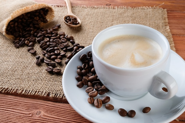 Kaffee auf einem holztisch tasse mit cappuccino auf dem tisch
