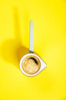 Kaffee auf gelbem tisch, flach gelegen, draufsicht
