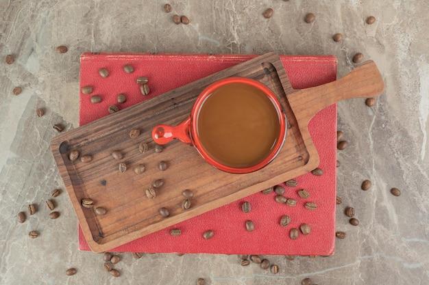 Kaffee auf holzbrett mit kaffeebohnen und buch