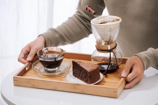 Kaffee auf holztablett mit schokoladenkuchen tropfen. kaffeezeit im café mit natürlichem licht